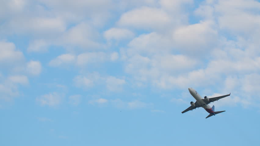 The plane takes off against a blue sky.