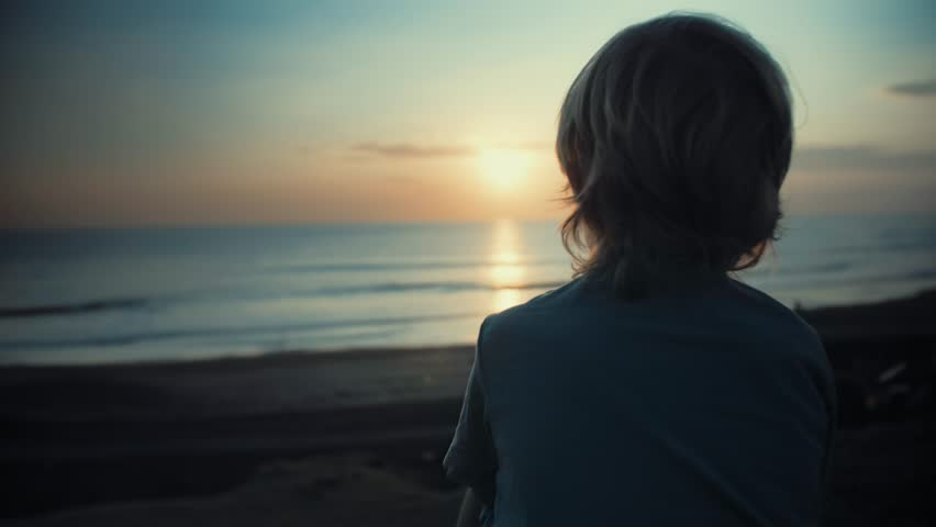 Child admiring beautiful sunset on shore. Looking at ocean view, thinking about life, dreaming. Happy childhood. Enjoying afternoon peace and nature. Quiet, calm mood. Vacation travel #1024489139