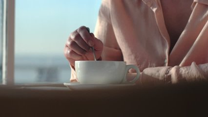 Close up of woman hands putting sugar on a coffee cup and stiring, in a cafè, by a big window. 4K video