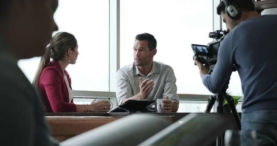 Happy businessman during corporate interview with female journalist. Manager answering question in office. Young woman at work as reporter with business man and filmmaker recording with video camera #1024511918