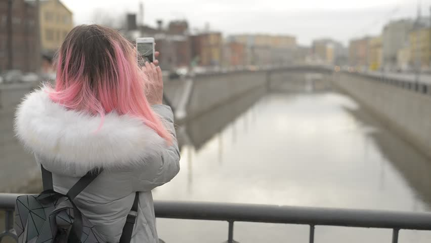 Pretty, young beautiful girl with pink hair make photo on the bridge  into the wind | Shutterstock HD Video #1024514399