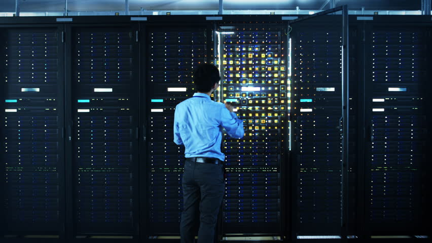 The Concept of Digitalization of Information: IT Specialist Standing In front of Server Racks with Laptop, He Activates Data Center with a Touch Gesture. Animated Visualization of Network Data