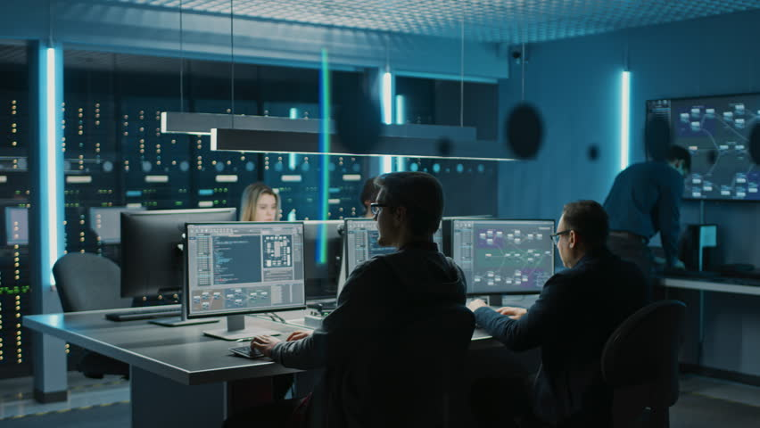 Team of IT Programers Working on Desktop Computers in Data Center Control Room. Young Professionals Writing on Sophisticated Programming Code Language. Elevated Moving Camera Shot Royalty-Free Stock Footage #1024519529