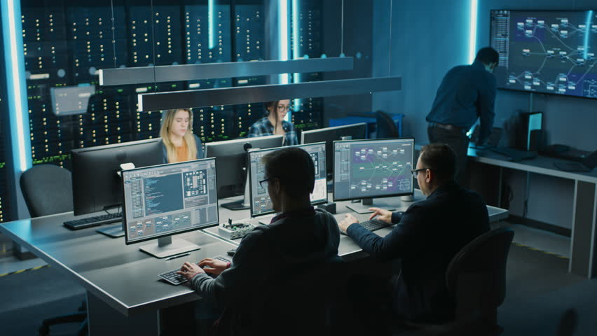 Team of IT Programers Working on Desktop Computers in Data Center Control Room. Young Professionals Writing on Sophisticated Programming Code Language. Elevated Moving Camera Shot Royalty-Free Stock Footage #1024519535