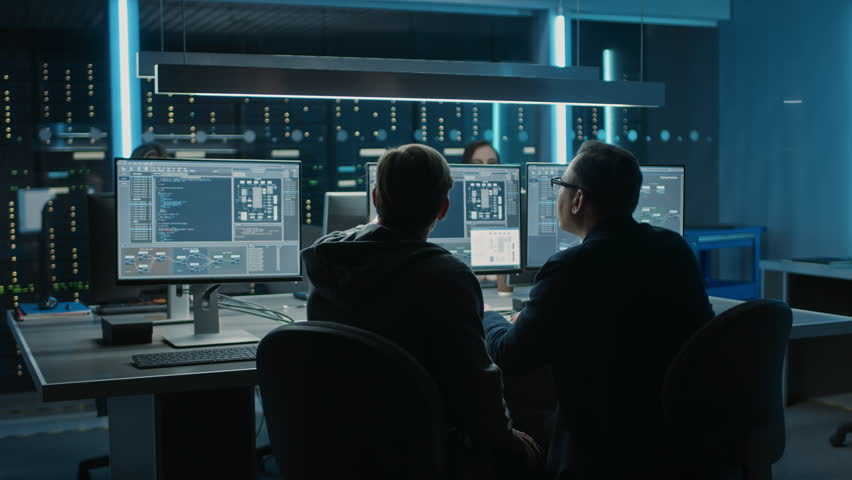 Two Professional IT Programers Discussing Blockchain Data Network Architecture Design and Development Shown on Desktop Computer Display. Working Data Center Technical Department with Server Racks | Shutterstock HD Video #1024519622