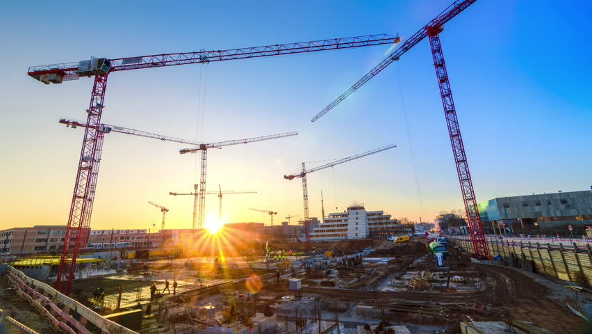 Timelapse footage of a large construction site with several busy cranes at dusk, with clear blue sky and the setting sun