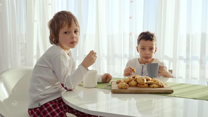 Two boys having breakfast in modern kitchen. Boy eat cookie with milk. White Table in Kitchen. Mother and two sons have breakfast. Cookies with milk | Shutterstock HD Video #1024521164