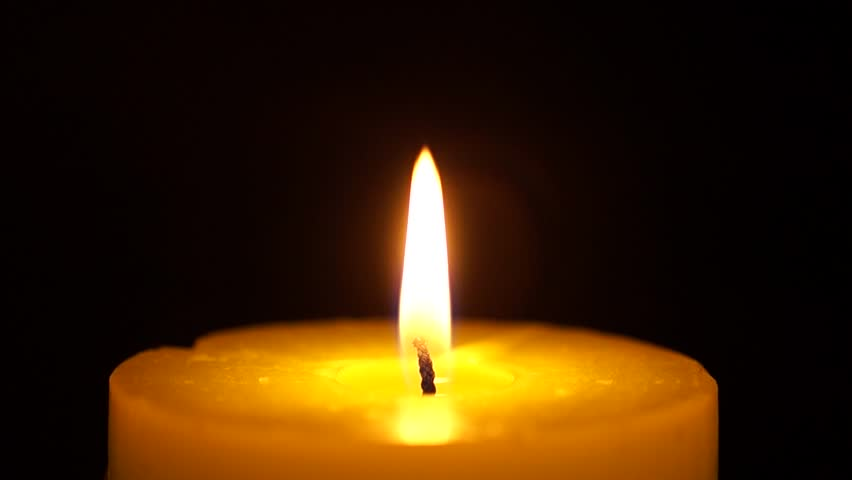 Beautiful fire of a candle in a dark room, a warm yellow candle quietly burning in the dark, a candle burning in the dark, the fire of a candle in the dark