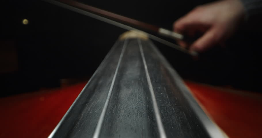 Slow motion artistic macro of master artisan luthier playing with a bow on a handmade violin or cello. Shot in 8K. Concept of spiritual instrument, art, orchestra, passion for music, sound, precision | Shutterstock HD Video #1024524677