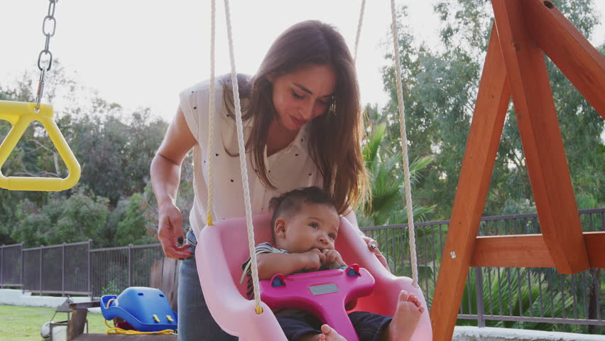 Young Hispanic mother pushing her baby on a swing at a playground in the park, close up | Shutterstock HD Video #1024534592