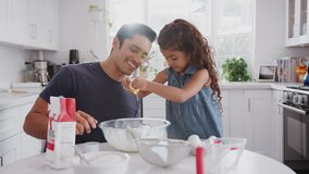 Jump cut clip of father and young daughter preparing cake mix in their kitchen, close up