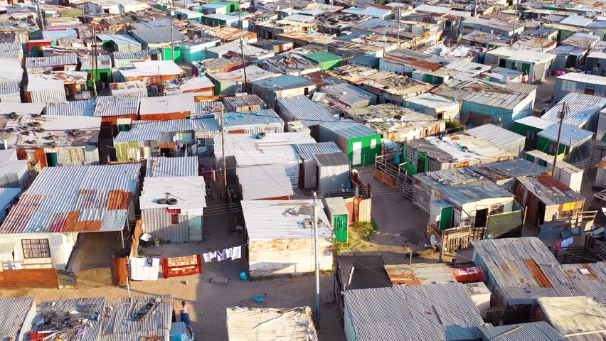 GUGULETHU, SOUTH AFRICA - CIRCA 2018 - Aerial over ramshackle tin roofs of Gugulethu, one of the poverty stricken slums.