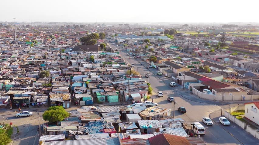 GUGULETHU, SOUTH AFRICA - CIRCA 2018 - Aerial over townships of South Africa, with poverty stricken slums, streets and ghetto buildings.