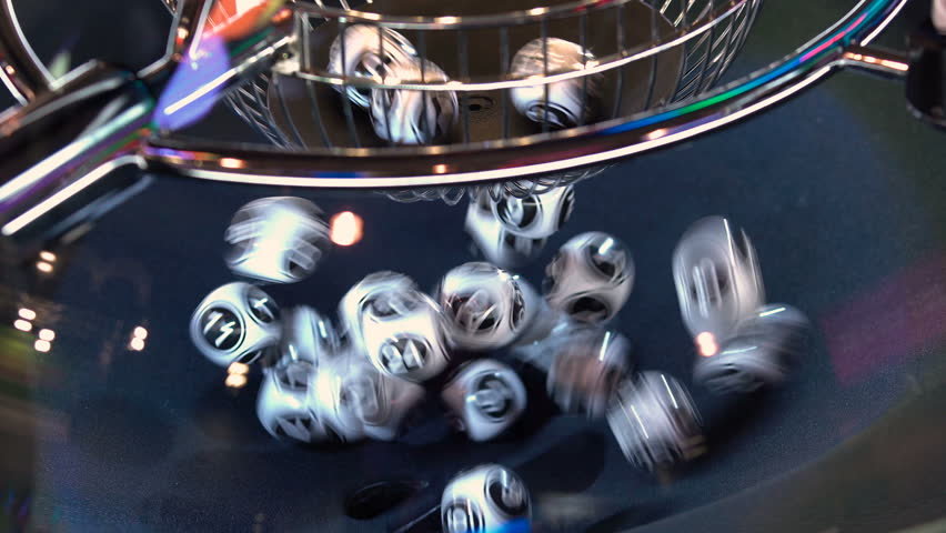 Black and white lottery balls in a rotating bingo machine. Lottery balls in a sphere in motion. Gambling machine and euqipment. Blurred lottery balls in a lotto machine. 4k