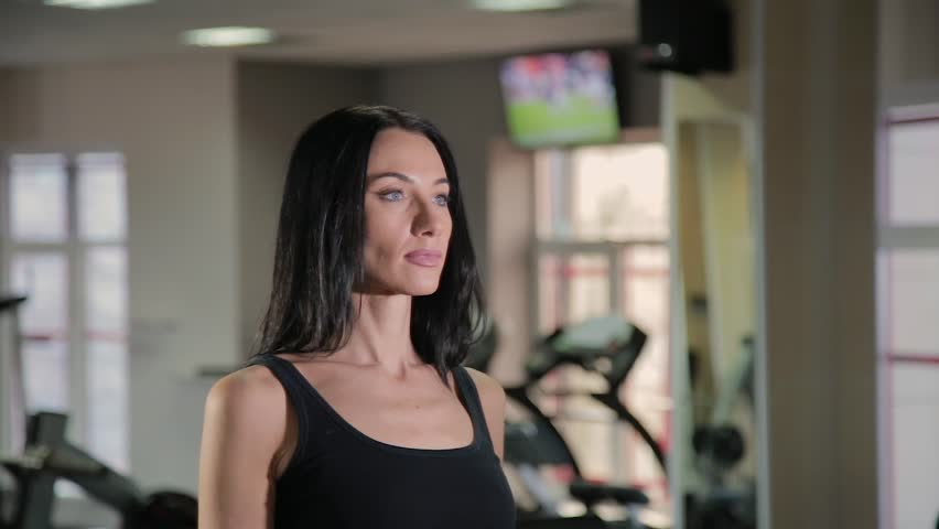 Beautiful athletic young girl trains dumbbells biceps in the gym. | Shutterstock HD Video #1024553108