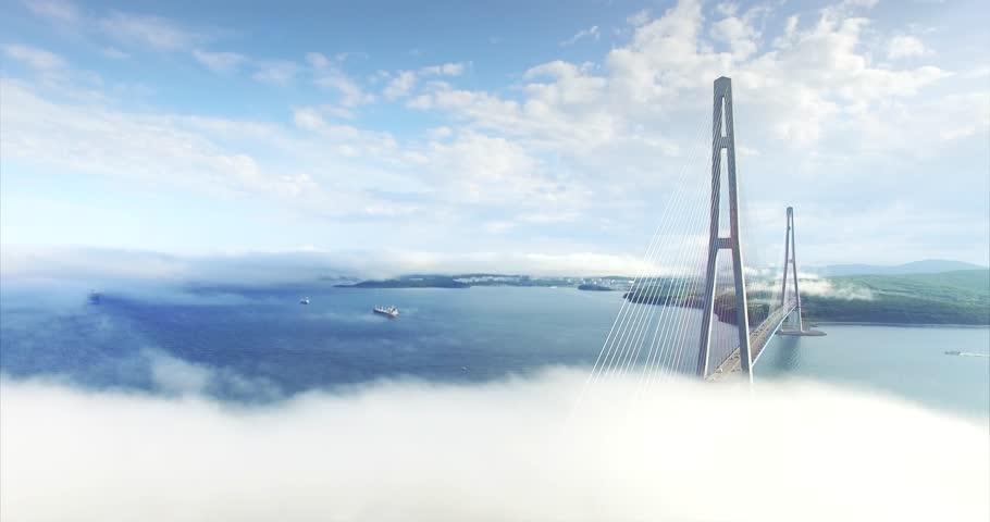 Beautiful aerial view of Russian bridge, longest cable-stayed bridge in the world. It connects Russky Island and Vladivostok across the Eastern Bosphorus strait. Light morning fog and clouds above it | Shutterstock HD Video #1024557167