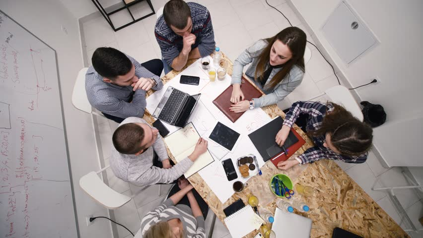 colleagues having creative meeting, hand shaking and cheering. view from above  #1024559405