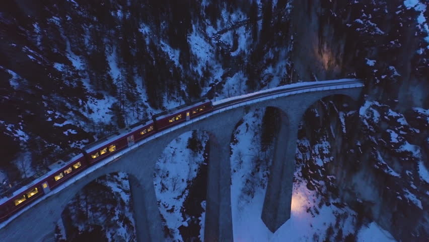 Landwasser Viaduct with Railway and Train at Winter Evening. Swiss Alps, Switzerland. Mountains, Forest and River. Aerial View. Drone Flies Forward, Camera Tilts Down