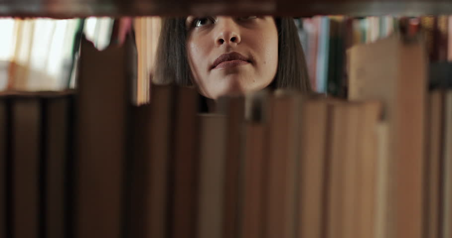 Female university student searching for book on bookshelves in library