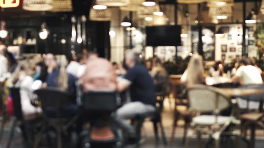 Blurred picture of the interior of a large beautiful restaurant with bright lighting. The waitress comes to the table and gives the visitors a menu and goes for drinks. Defocused restaurant