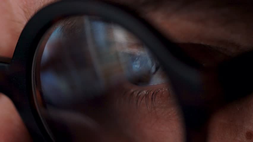 Man in glasses looking on the monitor and surfing Internet. The monitor screen is reflected in the glasses | Shutterstock HD Video #1024578164