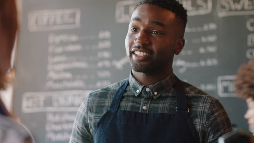 Young african american barista man serving customers in cafe using smart watch making contactless payment buying coffee spending money enjoying service | Shutterstock HD Video #1024583639