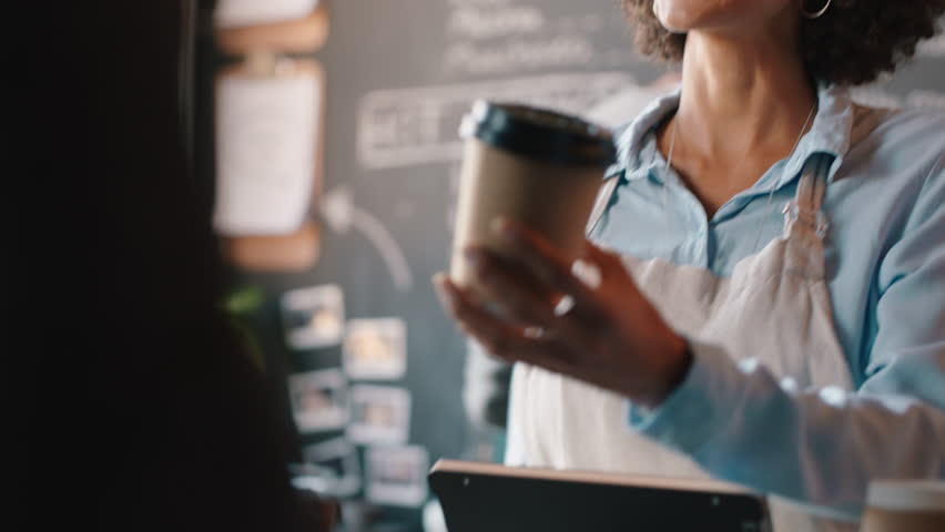 Beautiful barista woman serving customer using credit card making contactless payment buying coffee spending money in cafe | Shutterstock HD Video #1024583693