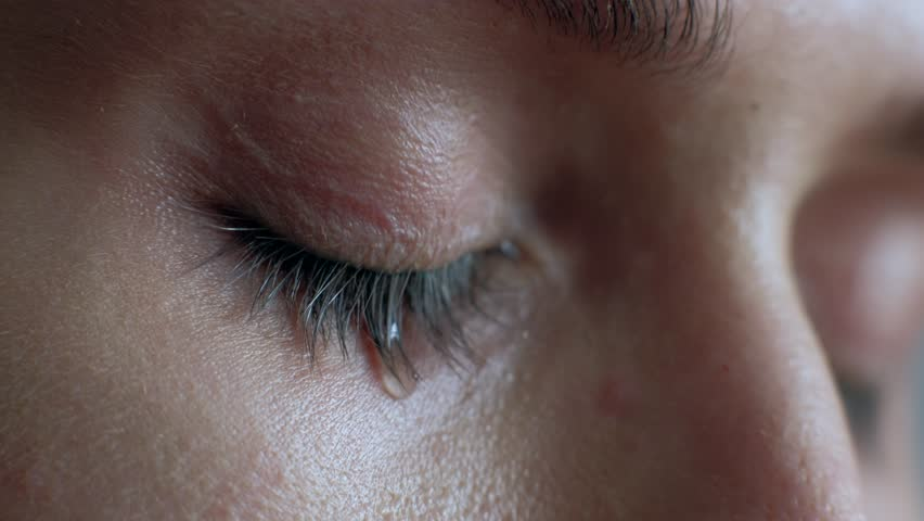 The female eye cries and tears are flowing macro video. Close-up woman eye cries and tears flow. 4k. Macro shoot.