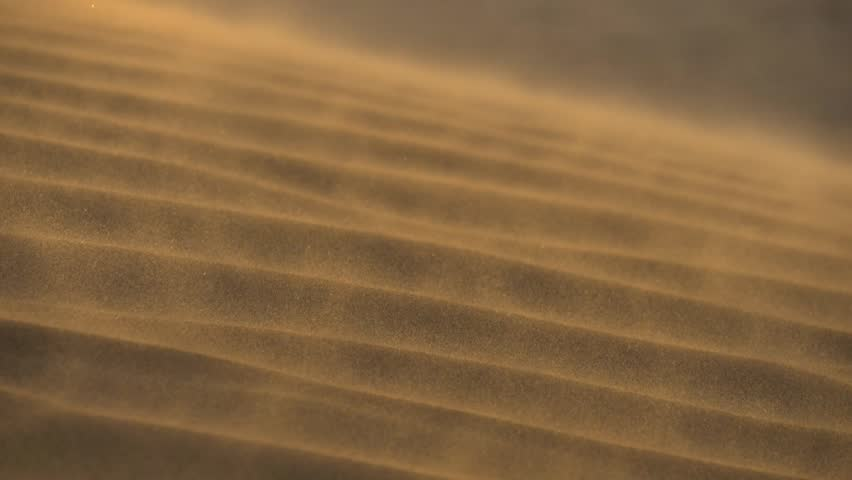 Sand waving in the wind in dunes in desert. Slow motion shot
