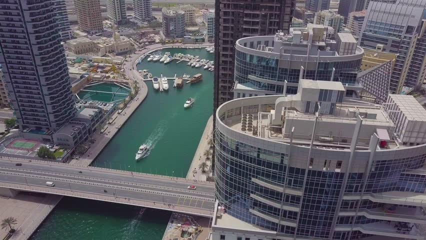 Bridge over the bay with passing cars and yachts on the background of the pier in Dubai. | Shutterstock HD Video #1024594220