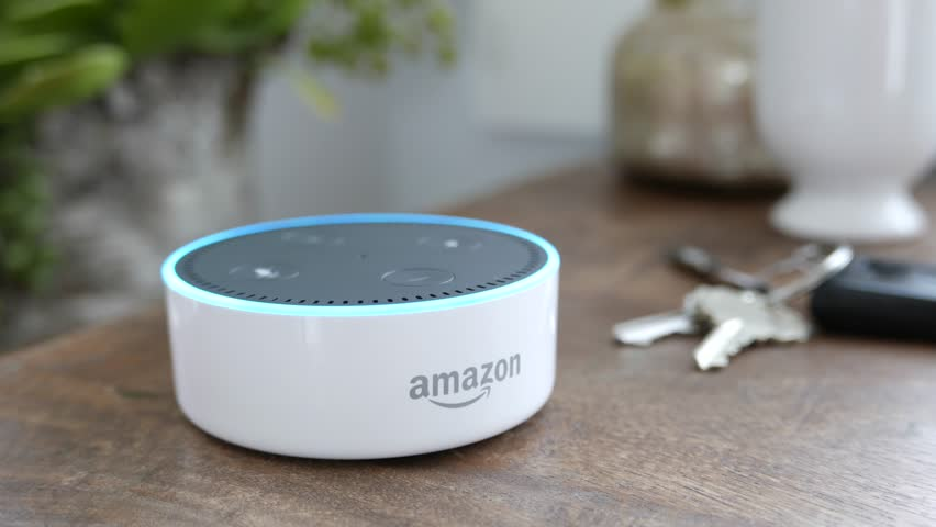 Los Angeles, CA, USA -02/21/19: Amazon Echo Dot on Tabletop. Amazon Echo Dot lights up with a blue light ring after a command on a tabletop. For editorial use.