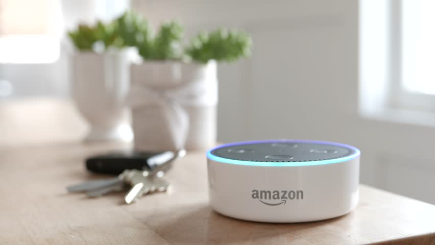 Los Angeles, CA, USA -02/21/19: Amazon Echo Dot on Tabletop. Amazon Echo Dot sits in front of keys on a wood table. Blue light ring. For editorial use.