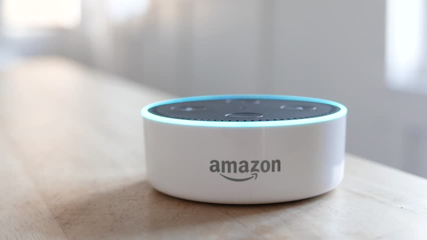 Los Angeles, CA, USA -02/21/19: Amazon Echo Dot on Tabletop. Amazon Echo Dot lights up with a command after it is revealed in frame. For editorial use.