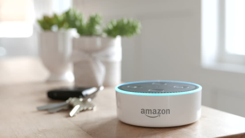 Los Angeles, CA, USA -02/21/19: Amazon Echo Dot on Tabletop. Tilting reveal of Amazon Echo Dot as it sits on a kitchen table. Blue light ring. For editorial use.