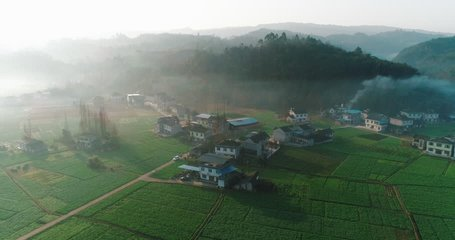 Aerial View: beautiful countryside landscape in the early spring morning of village, fields at the bottom of a mountain in mist at dawn, car parking on the country road, in Sichuan China,4K Drone clip