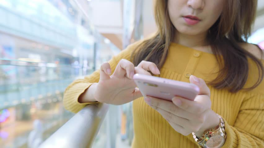 Young Woman Use Of Mobile Phone In Shopping Mall | Shutterstock HD Video #1024608605