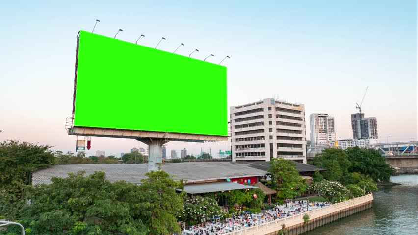 Green screen of advertising billboard on restaurants near river of twilight in Bangkok, Thailand. time lapse.