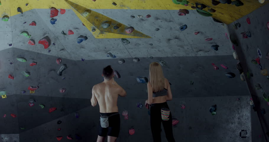 Caucasian male and female athletes preparing for bouldering at a climbing gym, discussing climbing strategy. 4K UHD | Shutterstock HD Video #1024626950
