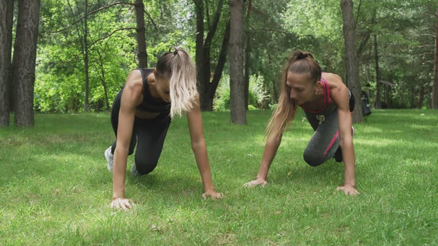 Two young beautiful women are doing plank exercise in park, fitness models exercising #1024643915
