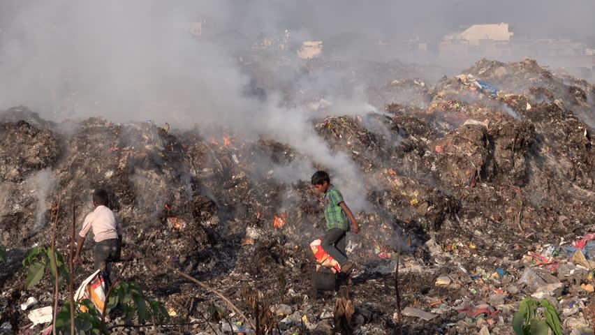 RISHIKESH, UTTARAKHAND, INDIA - DEC 19: Children recycling trash among toxic smoke at dumping ground on December 19, 2018 in Rishikesh, Uttarakhand, India