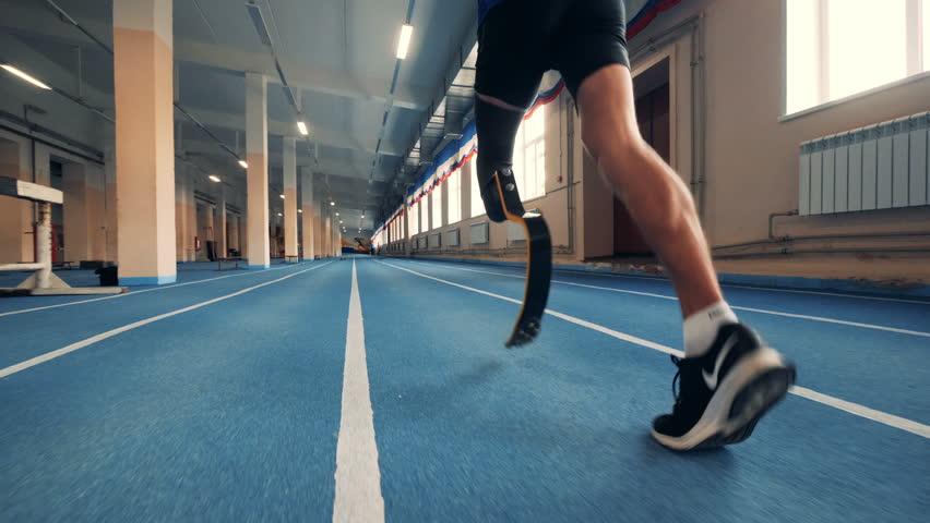 Nizhny Novgorod, Russia - CIRCA November 2018: Gym track and an athlete with a prosthetic leg running along it