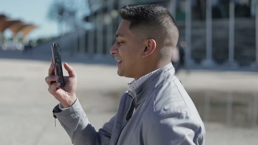 Smiling young man having video call through broken smartphone. Slow motion shot of happy middle eastern brunet talking to interlocutor though phone while walking on street. Communication concept | Shutterstock HD Video #1024654505