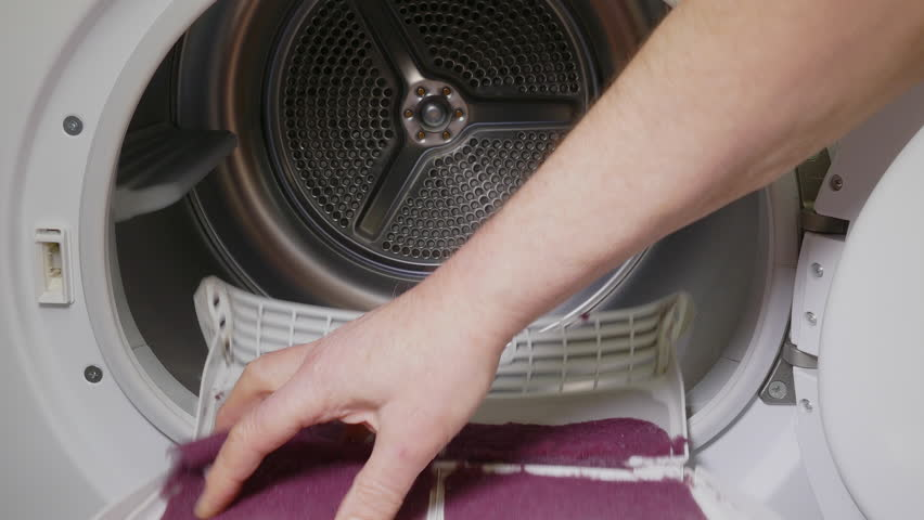 Close POV shot of a man's hands opening the door of a domestic tumble dryer, then removing the filter from the rim to scrape off the build-up of accumulated, lint / fluff. | Shutterstock HD Video #1024657880