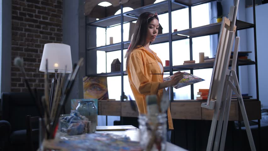 Inspired lovely female artist with colored palette creating artwork in workshop. Professional woman painter with paintbrush and palette drawing picture on canvas, expressing visions and imagination. | Shutterstock HD Video #1024666712