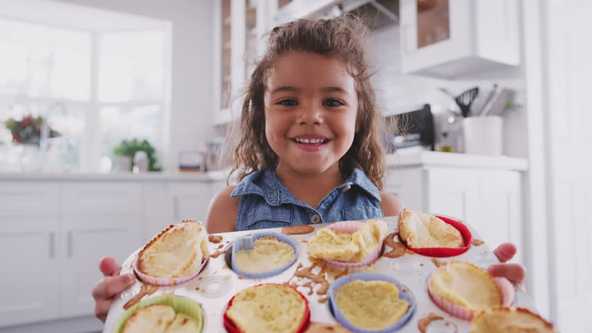 Happy young Hispanic girl standing in kitchen presenting the cakes she?s made to camera, close up