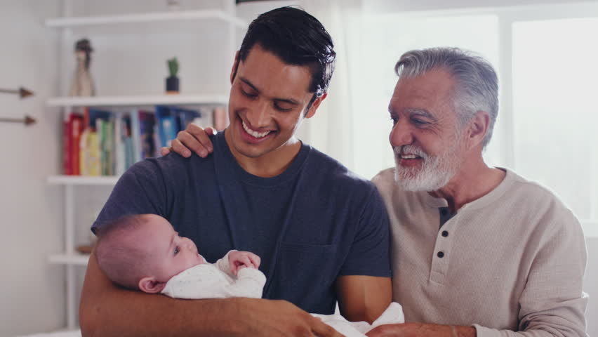 Proud Hispanic father holding his four month old son at home, with grandfather beside them, close up Royalty-Free Stock Footage #1024667303