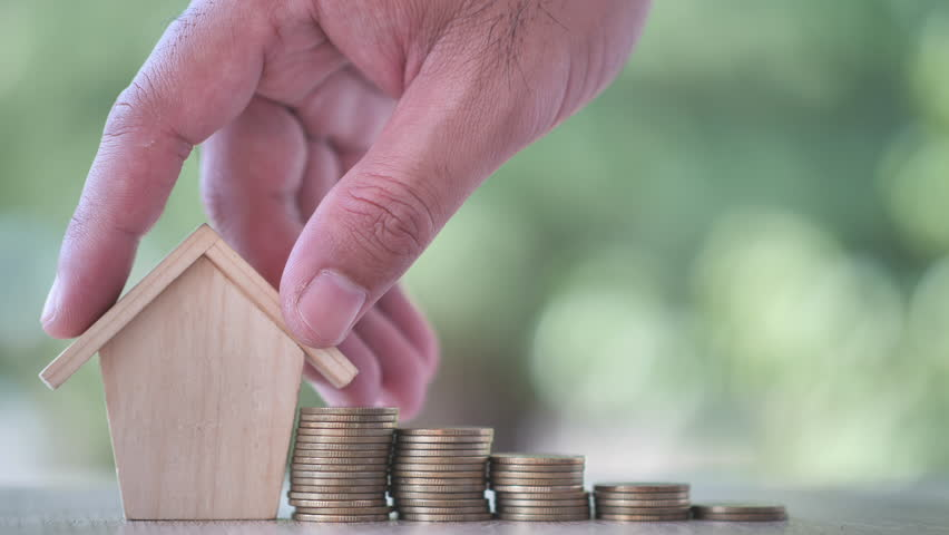 Hand putting house with Money coin on nature green background. Property investment and house mortgage financial, Credit home concept. Slow Motion | Shutterstock HD Video #1024686353