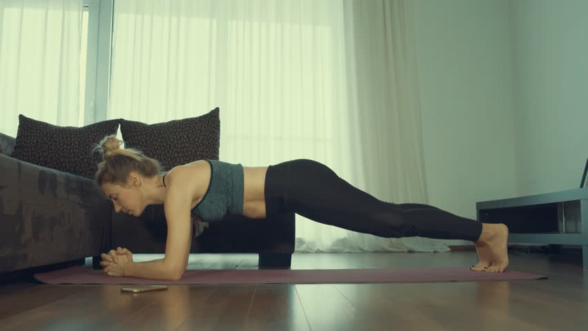 Young woman doing sports at home, Female fitness training in sportswear in the room    Shutterstock HD Video #1024689827