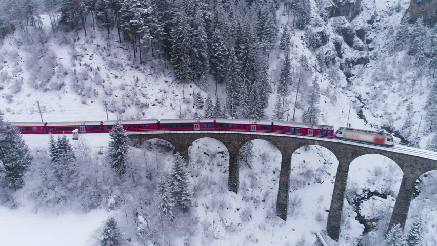 Viaduct and Train at Winter Day in Swiss Alps. Snowing. Switzerland. Aerial View. Drone Flies Forward and Downward
