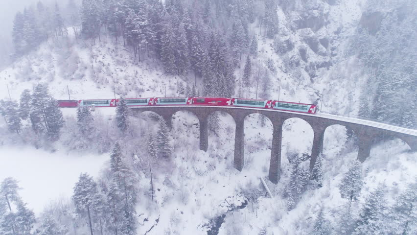 GRAUBUNDEN, SWITZERLAND - FEBRUARY 11, 2019: Viaduct and Glacier Express Train in Winter Day. Snowing. Swiss Alps. Switzerland. Aerial View. Drone Follows Train